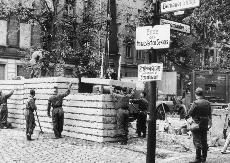 Seit 1963 wird an vielen Stellen, wie hier in der Bernauer Straße / Ecke Swinemünder Straße, die ursprüngliche Steinmauer durch eine Betonmauer ersetzt