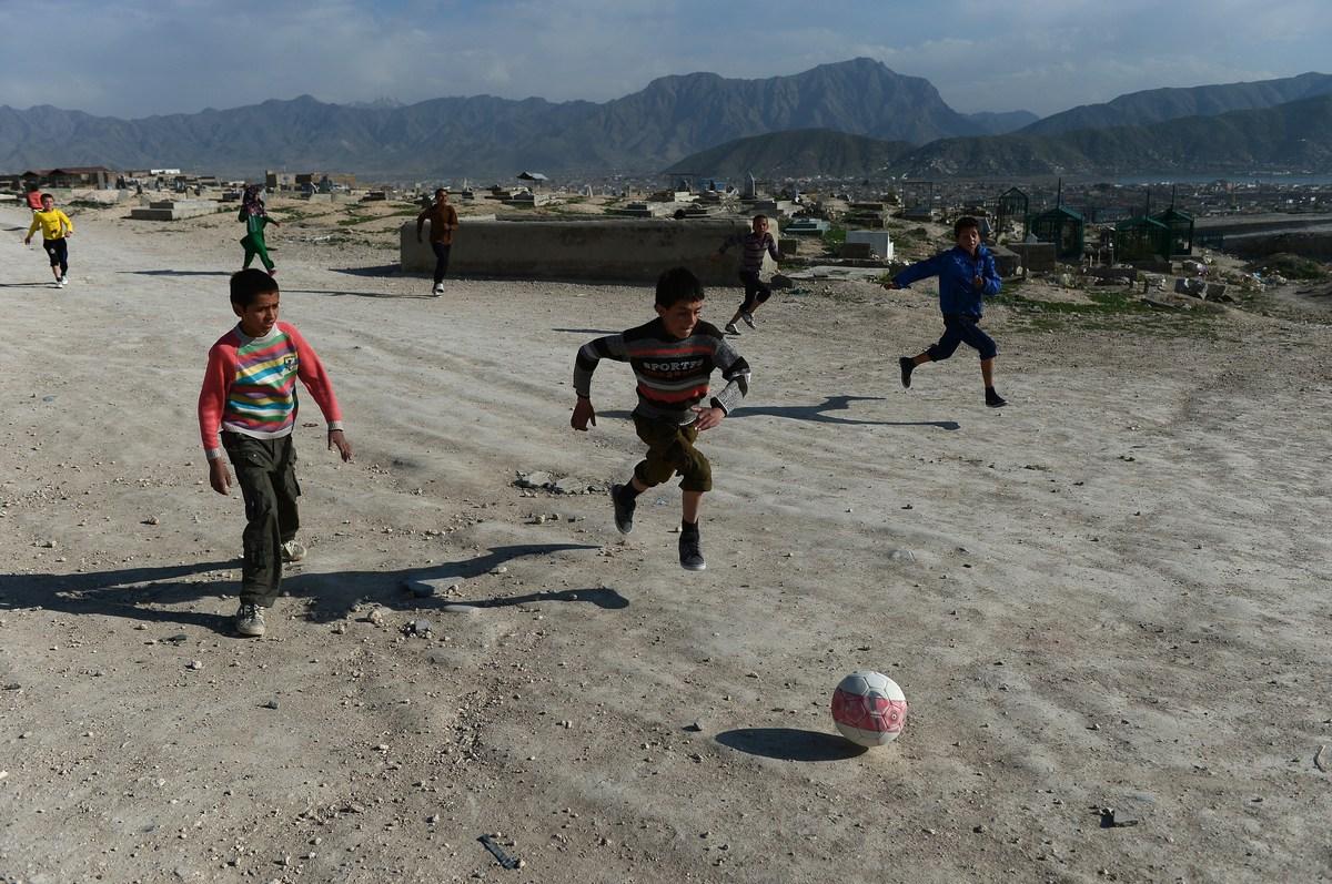 Bambini afgani giocano a pallone vicino a un cimitero sulle colline di Kabul, 12 aprile 2014