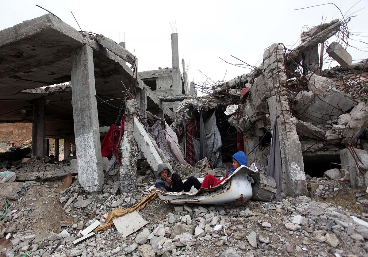 Bambini palestinesi giocano tra i detriti di una casa distrutta durante i bombardamenti israeliani. Siamo a Gaza, nel quartiere Shujaiyya, 6 gennaio 2015