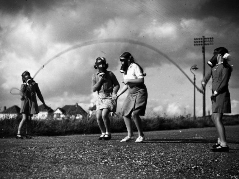 Un gruppo di ragazzine di Londra gioca indossando maschere antigas in un parco vicino a delle case temporanee nella costa sud dell'Inghilterra (1940)