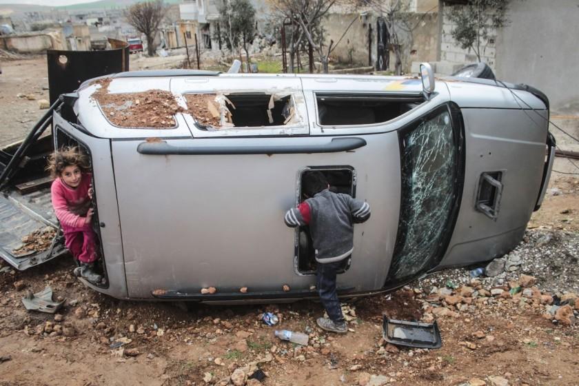 Un gruppo di bambini siriani gioca con un'auto distrutta nel centro di Kobane, in Siria. Foto scattata il 18 febbraio 2015