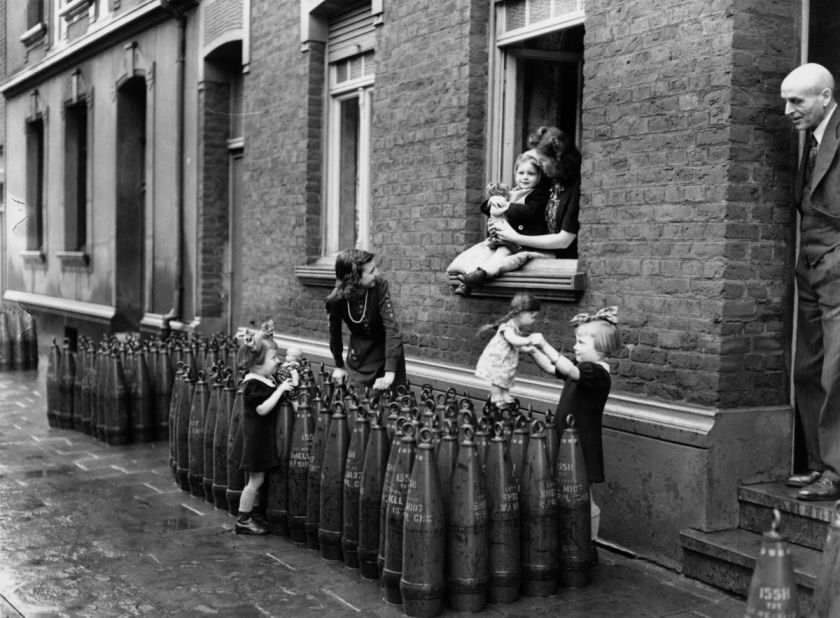 Monaco. Delle bambine giocano con le bambole su una schiera di missili depositati sotto la loro casa
