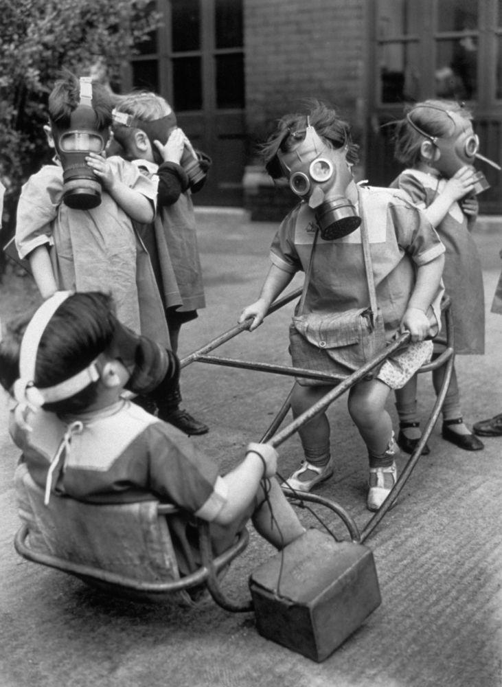 Bambini dell'asilo in un parco giochi con le maschere antigas, 1940