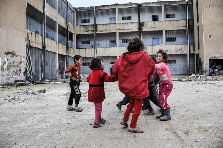 Bambini siriani giocano nel cortile di un palazzo distrutto nel centro di Kobane, 18 febbraio 2015