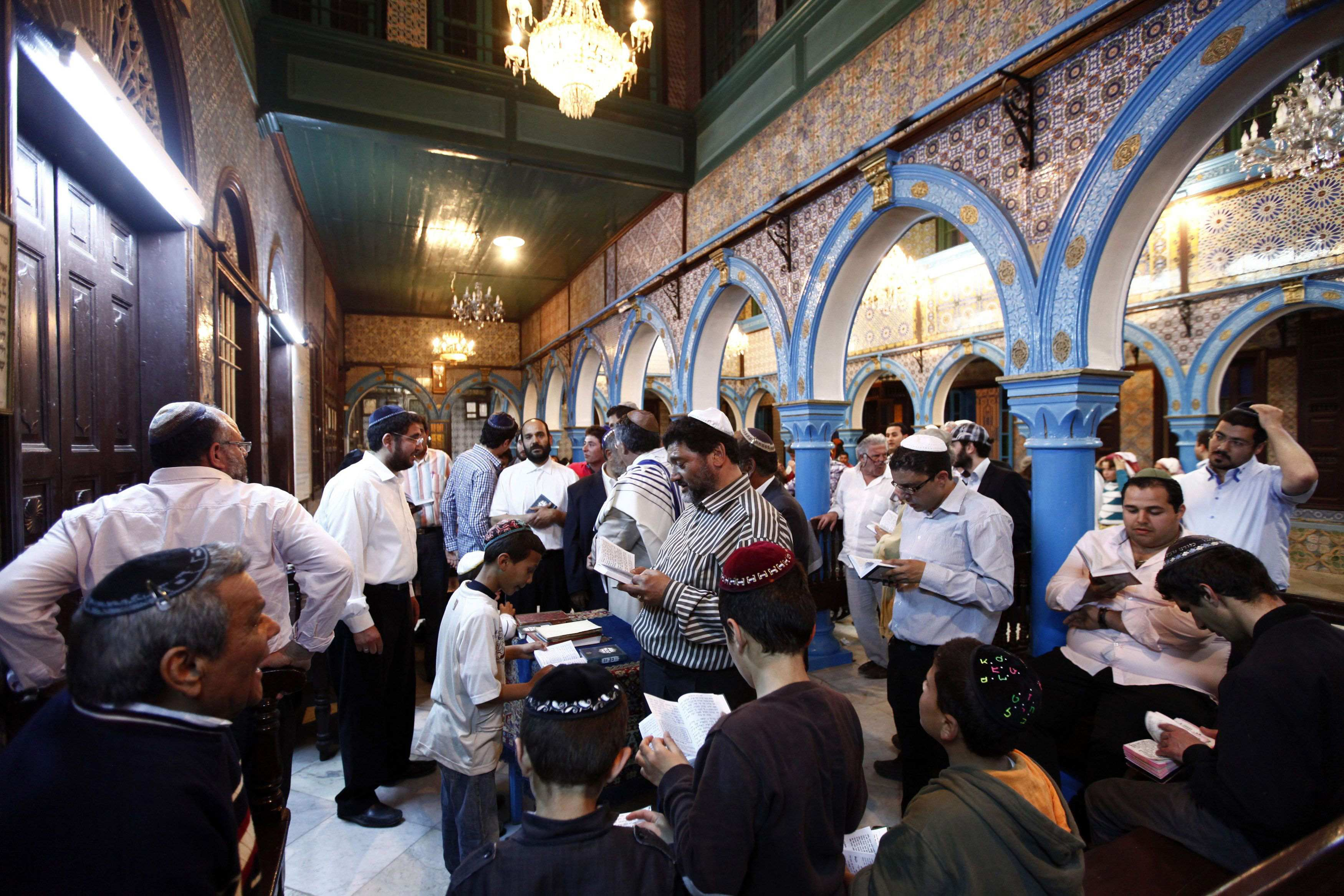 Jewish men pray inside the blue-tiled El Ghriba synagogue on the Tunisian island of Djerba following a wedding ceremony